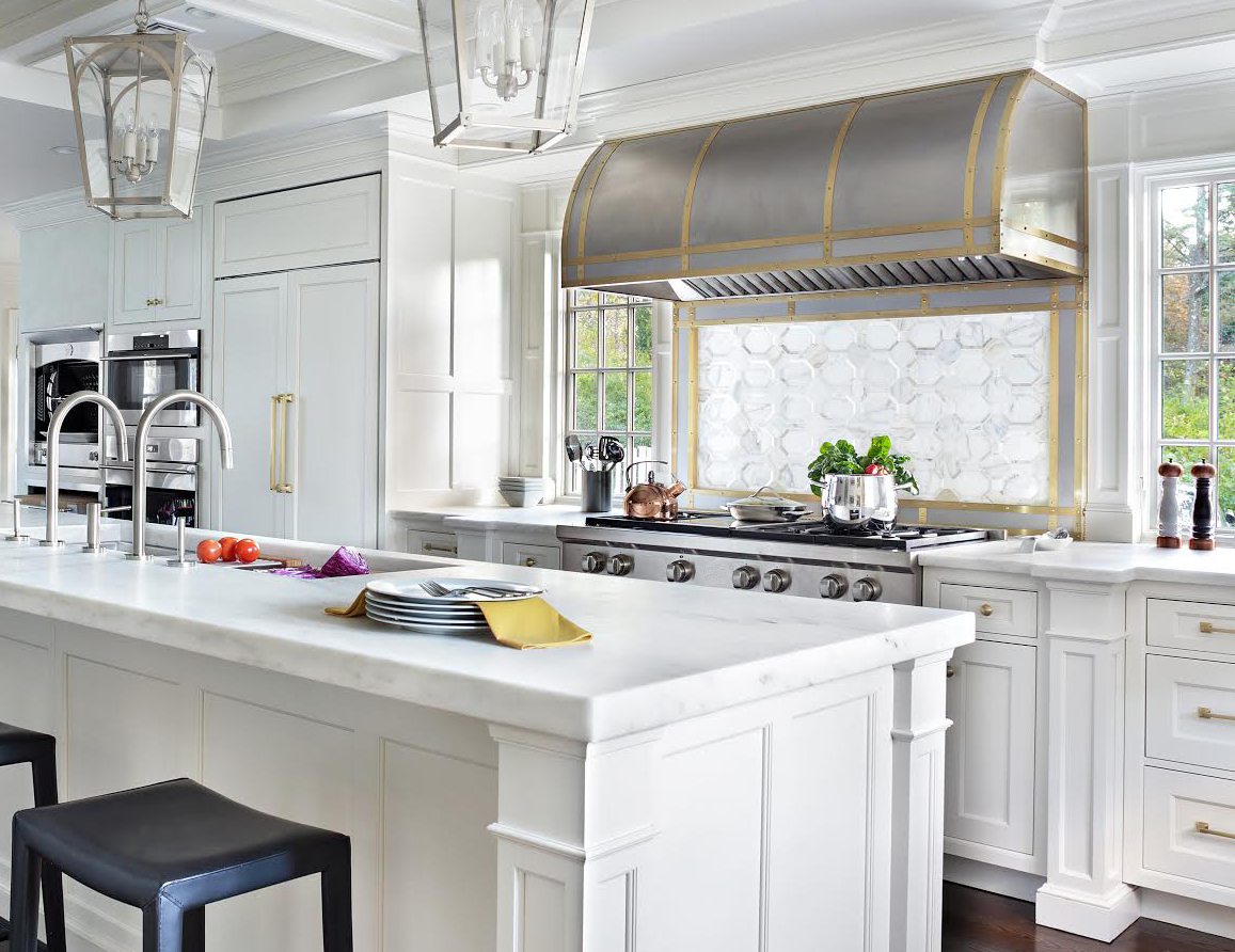 Wall mounted non-directional stainless steel Canopy style range hood with antique brass bands.