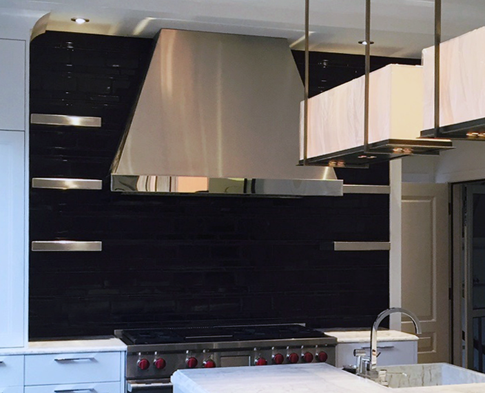 Stainless steel designer range hood with stainless steel floating shelves.